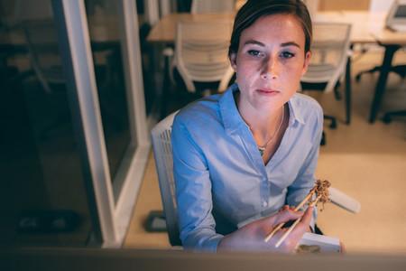 Woman entrepreneur sitting in office having dinner