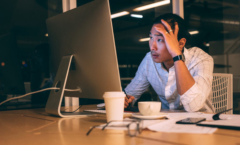 Businessman working late night in office looking stressed
