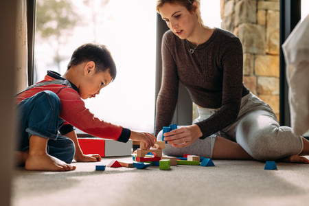 Mother and son playing with building blocks at home