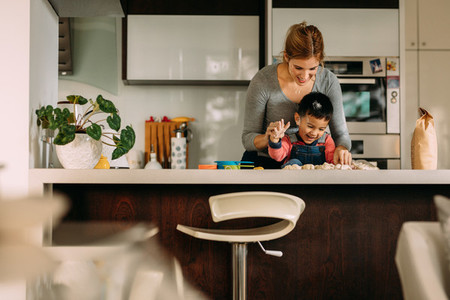 Little boy having fun making cookies with mother