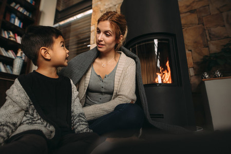 Young mother and son by a fireplace at home