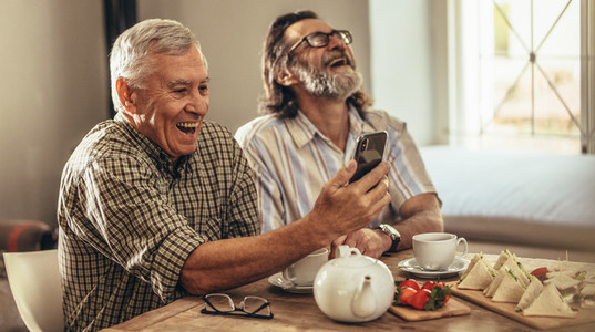 Retired men looking at old photographs on smartphone and laughin