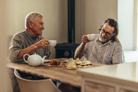 Retired friends enjoying tea and snacks at home