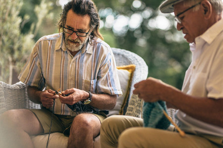 Retired male friends doing knitting for pastime