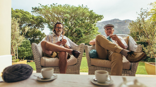 Senior men sitting relaxed on armchair and knitting