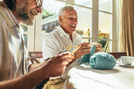 Senior friends enjoying knitting at home