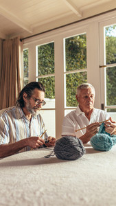 Senior friends knitting at home