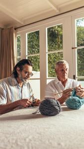 Senior friends knitting at home