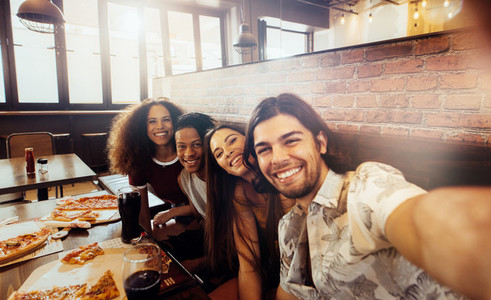 Group of multi ethnic friends making selfie at restaurant