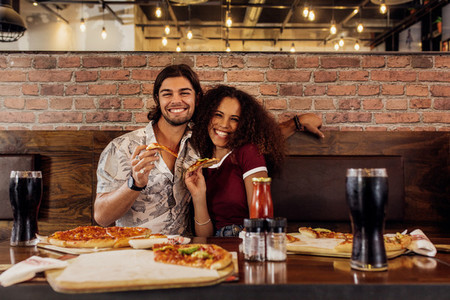 Smiling couple having pizza at cafe