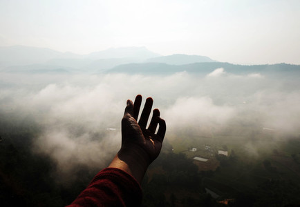 Hand on fog mountain background