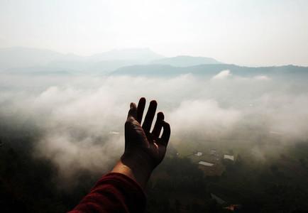 Hand on fog mountain background