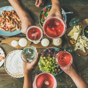 Flat lay of friends hands eating and drinking together  square crop