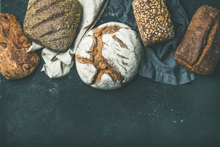 Various bread selection flat lay  black background  copy space