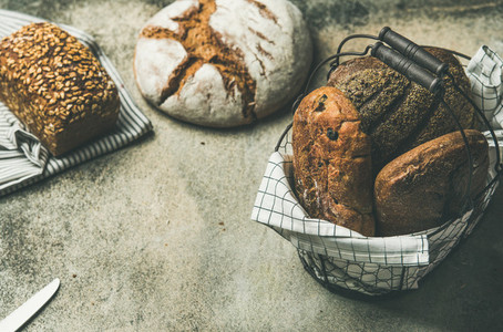 Various bread loaves on grey concrete background  copy space