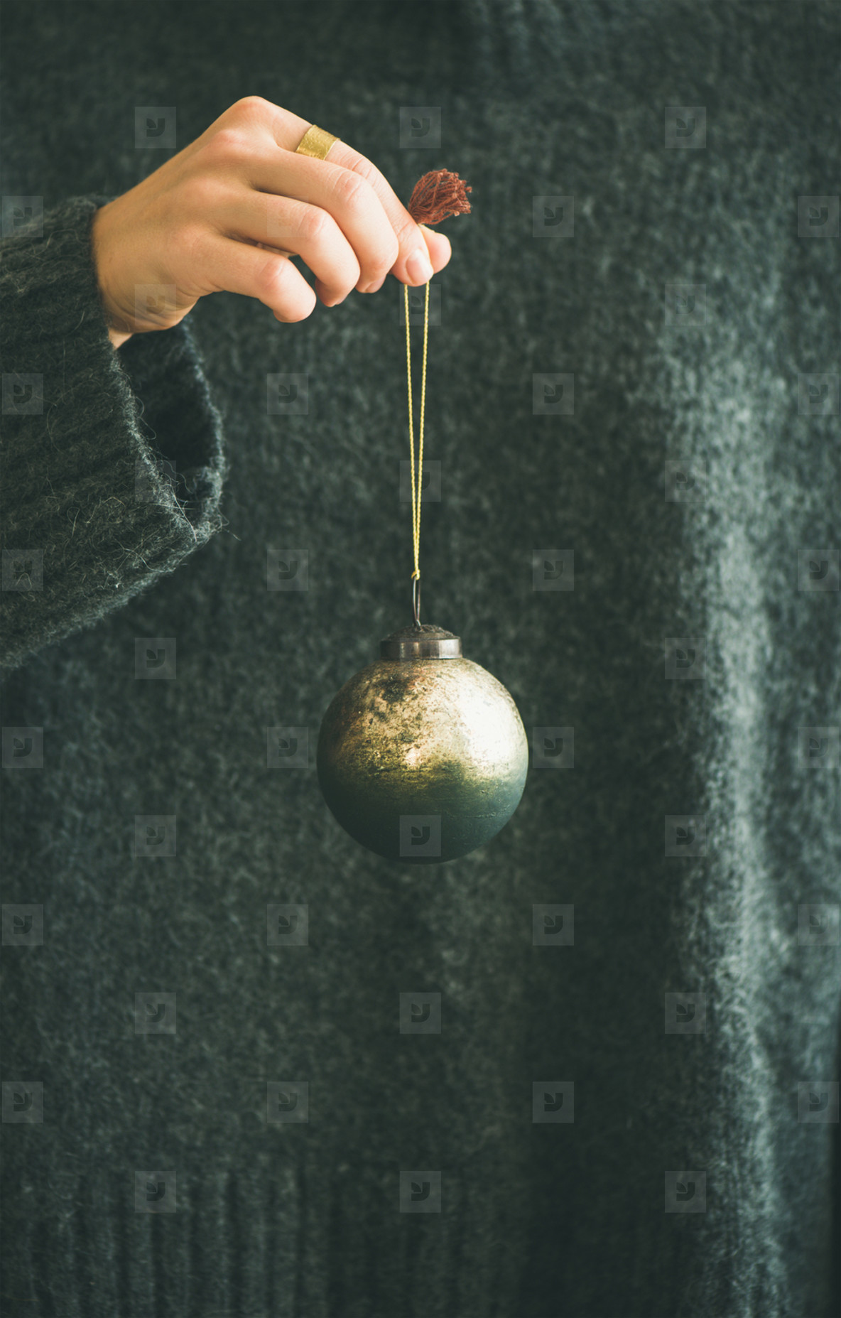 Woman in grey sweater holding decorative golden ball in hand