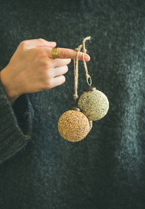 Woman in grey sweater holding decorative golden balls on finger