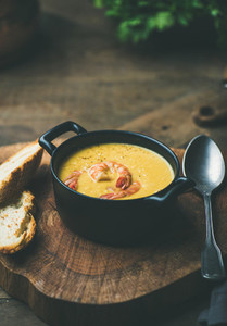 Corn creamy soup with shrimps served in pot copy space