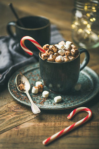 Christmas hot chocolate with marshmallows and cocoa on wooden background