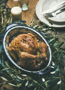 Whole roasted chicken decorated with olive tree branch on table