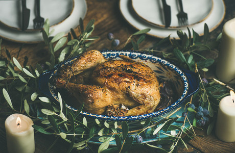 Whole roasted chicken with garlic decorated with olive tree branch