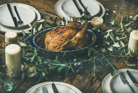 Whole roasted chicken for Christmas plates and candles