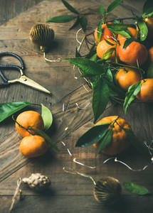 Fresh tangerines  decoration toys and light garland over rustic background