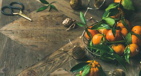 Fresh tangerines with leaves and decoration toys over wooden table
