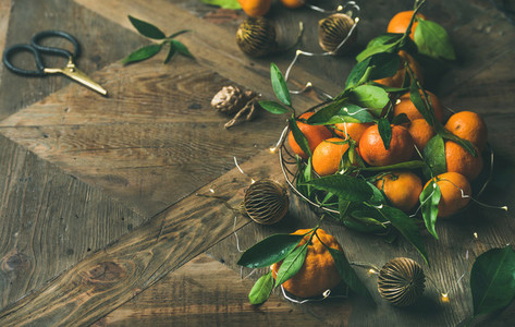 Fresh tangerines with leaves and decoration toys over table