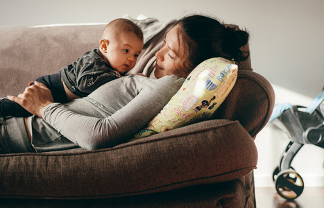 Woman lying on couch with her baby