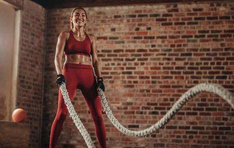 Smiling woman using battle ropes for exercising