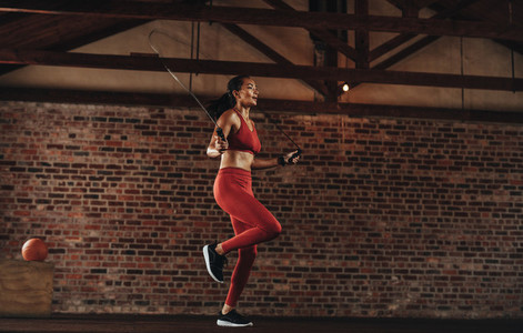 Healthy woman skipping rope at gym