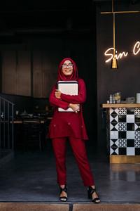 Muslim business woman standing at restaurant door