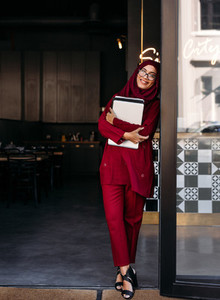 Muslim woman standing with laptop at coffee shop door