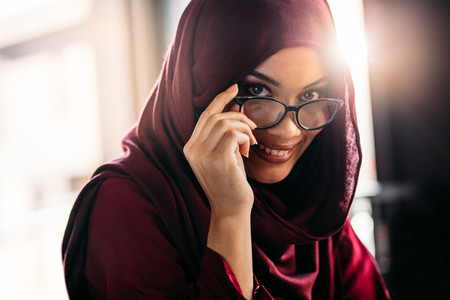 Islamic woman in hijab peeking through eyeglasses