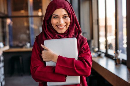 Cheerful islamic woman in hijab with laptop at cafe