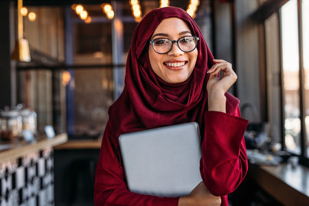 Smiling businesswoman in hijab at coffee shop