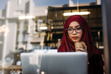 Hijab girl with coffee using laptop at cafe