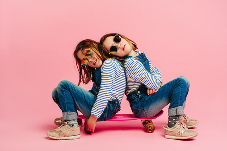 Adorable girls sitting together on a skateboard