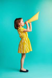 Girl speaking into paper megaphone