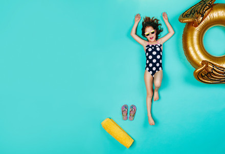 Happy girl in swimsuit lying on blue background