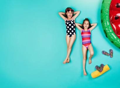 Small girls in swimwear relaxing on blue background