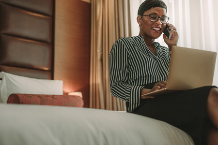 African businesswoman on tour working from hotel room