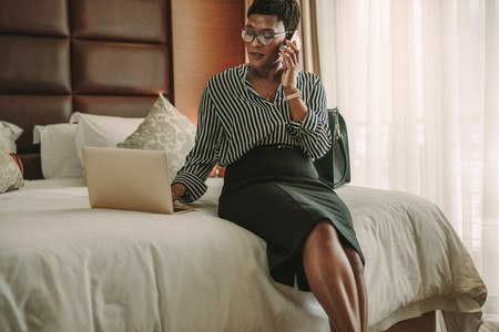 Business woman in hotel room using laptop and smartphone