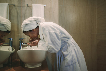 African woman in bathroom washing her face