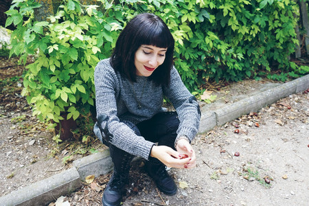 Beautiful caucasian brunette woman sitting on ground in a park w