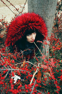 Portrait of a beautiful young brunette woman in red by a tree wi