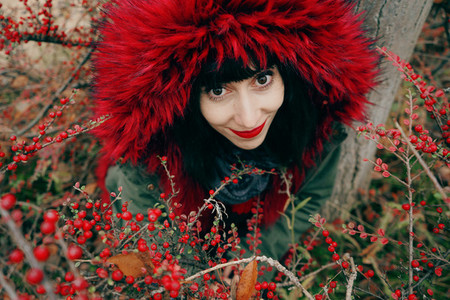 Portrait of a beautiful young brunette woman in red with a smile