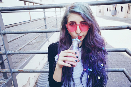 Happy beautiful teen with pink sunglasses drinks and enjoys a pi