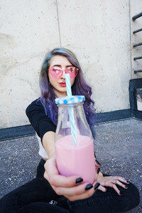 Happy beautiful teen with pink sunglasses cheers and enjoys a pi